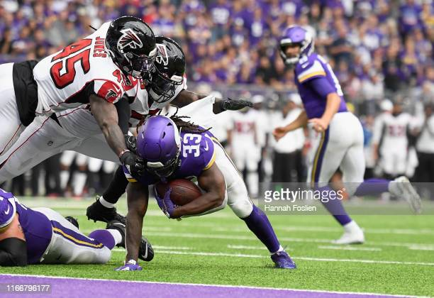 Richie Brown and De'Vondre Campbell of the Atlanta Falcons tackle Dalvin Cook of the Minnesota Vikings just short of the goal line during the second...
