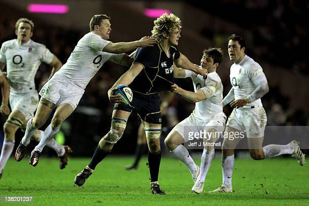 Richie Gray of Scotland offloads as he is tackled by Chris Ashton and Ben Foden of England during the RBS Six Nations match between Scotland and...