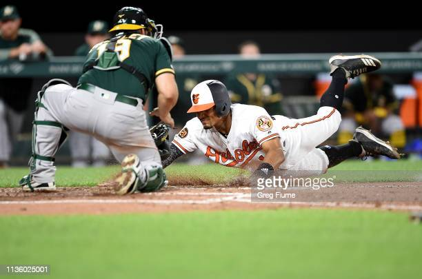 Richie Martin of the Baltimore Orioles is tagged out at home plate by Josh Phegley of the Oakland Athletics in the third inning at Oriole Park at...