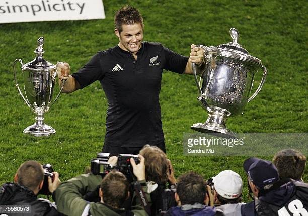 Richie McCaw, captain of the All Blacks holds the Bledisloe Cup and Tri-Nations trophy up for photographers after their win against the Wallablies in...