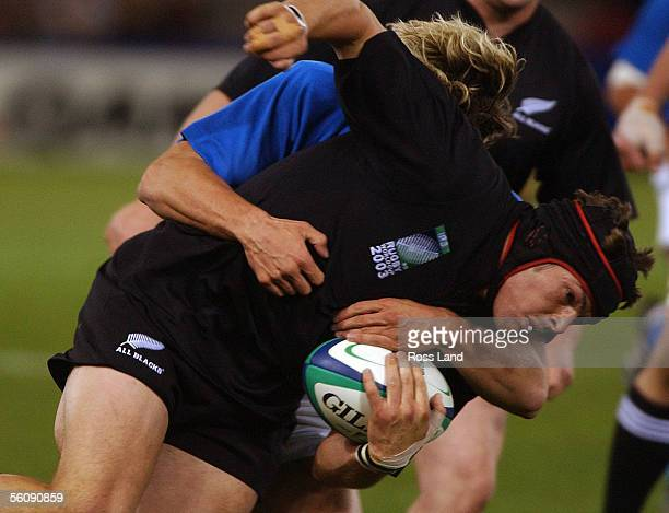 Richie McCaw is brought down in the tackle of Miro Bergamasco during the All Blacks 707 win over Italy in their Rugby World Cup match at the Telstra...