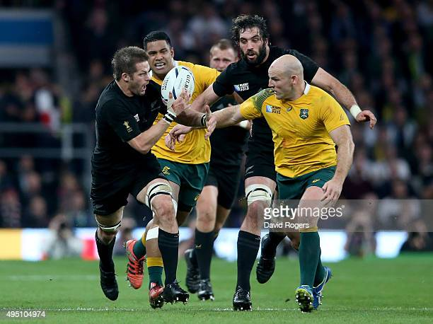 Richie McCaw of New Zealand is tackled by Stephen Moore of Australia during the 2015 Rugby World Cup Final match between New Zealand and Australia at...