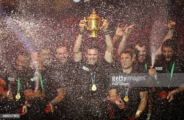 Richie McCaw of New Zealand lifts the Webb Ellis Cup as his teammates spray champagne after victory in the 2015 Rugby World Cup Final match between...