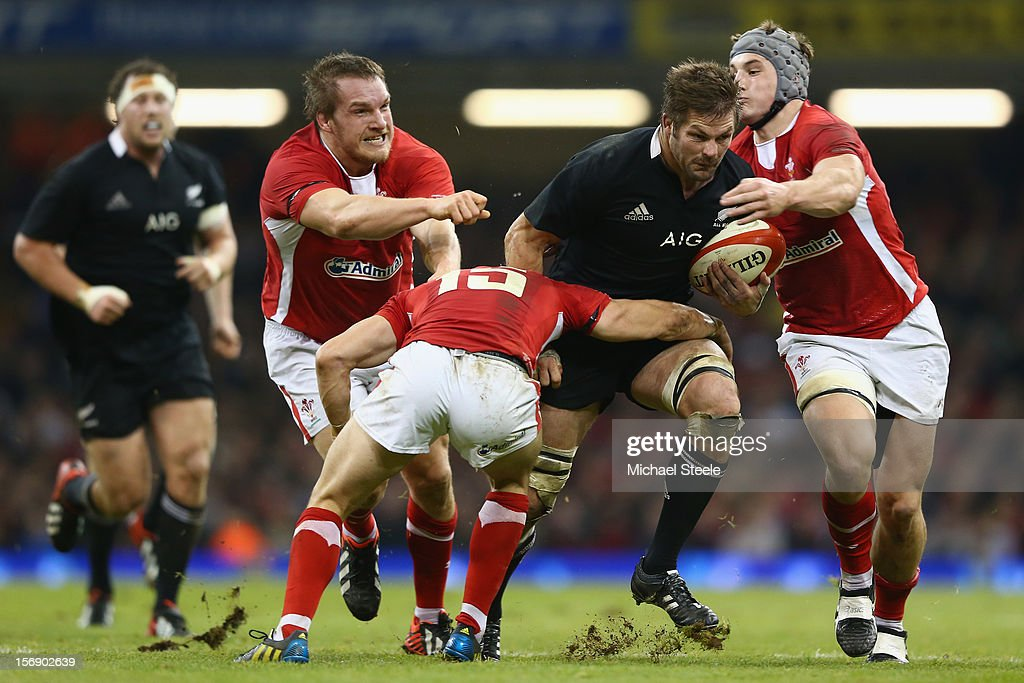 Richie McCaw (2R) of New Zealand powers through the challenge of Jonathan Davies (R), Leigh Halfpenny and Gethin Jenkins (L) of Wales during the International match between Wales and New Zealand at the Millennium Stadium on November 24, 2012 in Cardiff, Wales.
