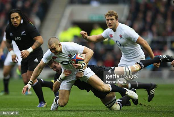 Richie McCaw of New Zealand tackles Mike Brown of England during the QBE International match between England and New Zealand at Twickenham Stadium on...
