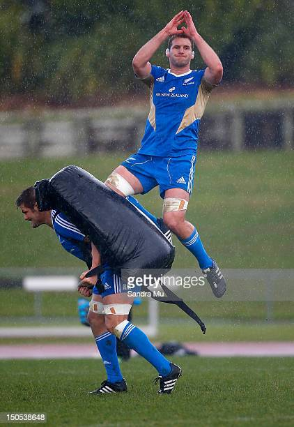 Richie McCaw of the All Blacks holds the pad for Kieran Read of the All Blacks during a New Zealand All Blacks training session at Trusts Stadium on...