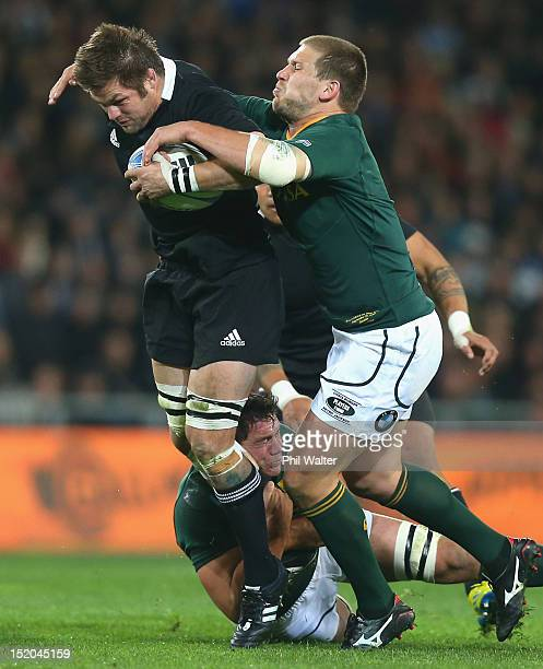 Richie McCaw of the All Blacks is tackled by Francois Steyn of South Africa during the Rugby Championship match between the New Zealand All Blacks...