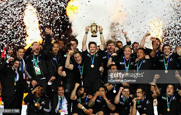 Richie McCaw of the All Blacks lifts the Webb Ellis Cup as team mates celebrate after the 2011 IRB Rugby World Cup Final match between France and New...