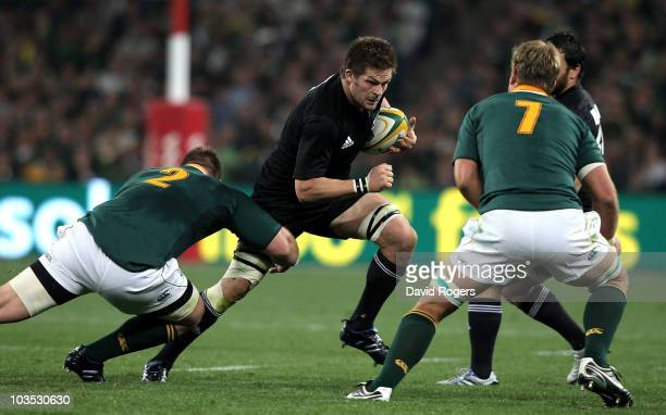 Richie McCaw of the All Blacks moves past John Smit during the 2010 TriNations match between the South African Springboks and the New Zealand All...