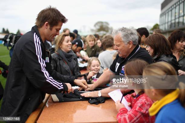 Richie McCaw of the All Blacks signs autographs for Christchurch residents who lost family and friends in the earthquake following a New Zealand All...