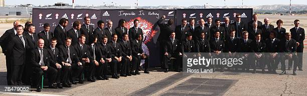 Richie McCaw of the New Zealand All Blacks signs an Adidas poster as the New Zealand squad pose for a team photo at Marseille airport after arriving...