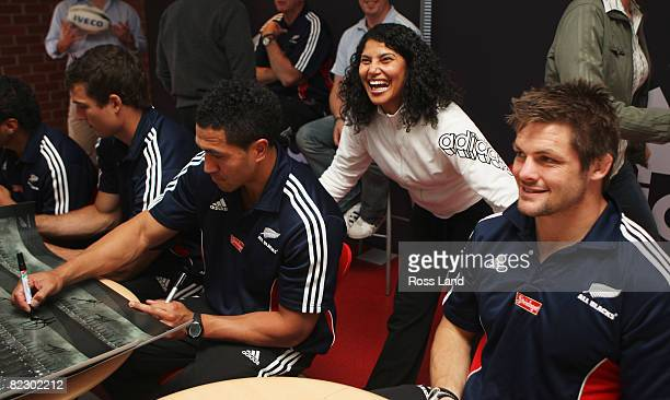 Richie McCaw poses for a photograph with a staff member as Anthony Boric and Mils Muliaina sign posters during a visit to the adidas factory...