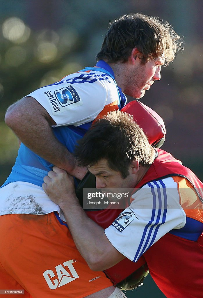 Richie McCaw tackles Tom Donnelly with tackle a bag during a Crusaders Super Rugby training session at Rugby Park on July 3, 2013 in Christchurch, New Zealand.