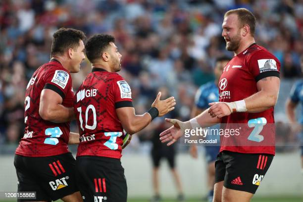 Richie Mo'unga of the Crusaders scores a try and celebrates with Codie Taylor and Joe Moody of the Crusaders during the round 3 Super Rugby match...