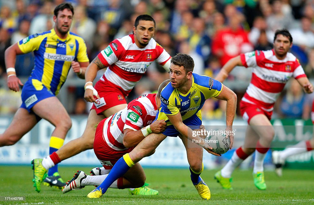 Richie Myler of Warrington looks to pass in the tackle of Wigan's Lee Mossop during the Super League match between Warrington Wolves and Wigan Warriors at the Halliwell Jones Stadium on June 24, 2013 in Warrington, England.
