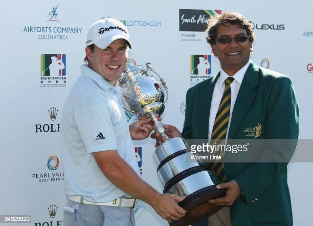Richie Ramsay of Scotland is awarded the trophy by Enver Hassen President of the South African Golf Association after winning the South African Open...