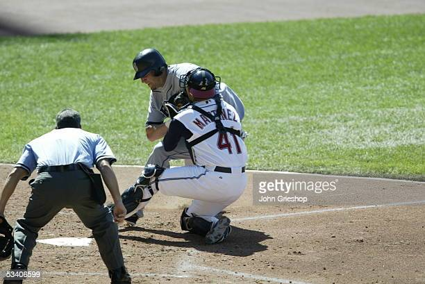 Richie Sexson of the Seattle Mariners collides with catcher Victor Martinez of the Cleveland Indians during the game at Jacobs Field on July 23 2005...