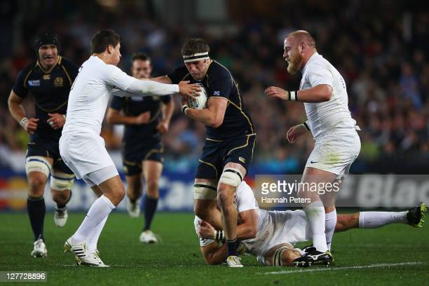 Richie Vernon of Scotland charges through Ben Foden and Dan Cole of England during the IRB 2011 Rugby World Cup Pool B match between England and...