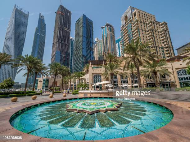 Richly coloured fountain of Arabic tile beneath the opulent residential towers of the Dubai Marina.