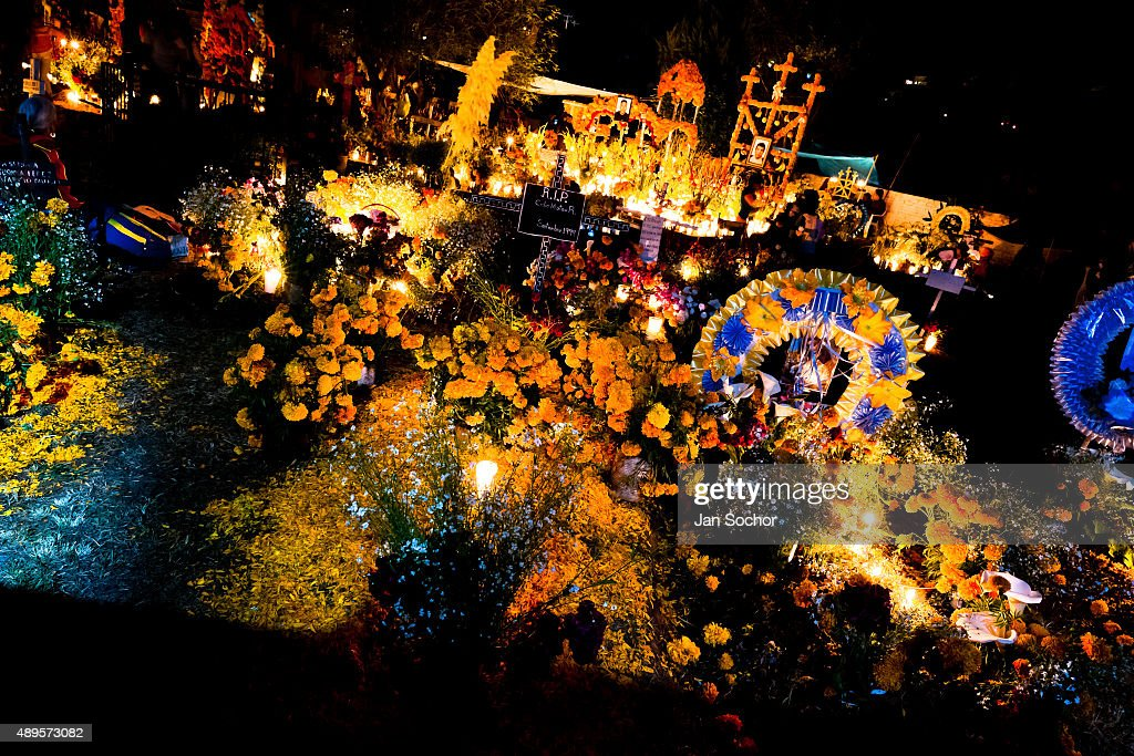 Richly decorated graves, covered by flowers, offerings and candles, are seen during the Day of the Dead celebration at the cemetery on November 02, 2014 in Tzintzuntzan, Mexico. Day of the Dead is a syncretic religious holiday, celebrated throughout Mexico, combining the death veneration rituals of the ancient Aztec culture with the Catholic practice. Based on the belief that the souls of the departed may come back to this world on that day, people gather on the gravesites praying, drinking and playing music, to joyfully remember friends or family members who have died and to support their souls on the spiritual journey.