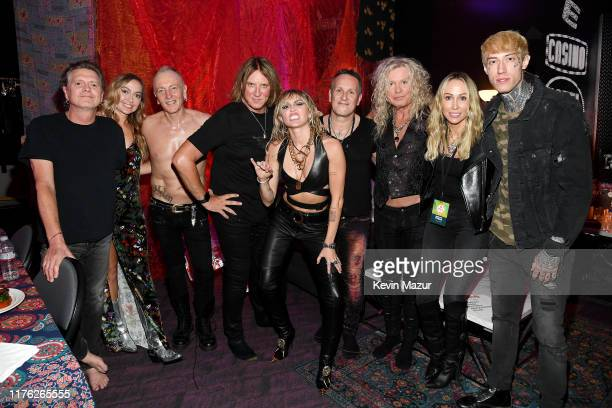 Rick Allen Brandi Cyrus Phil Collen Joe Elliott Miley Cyrus Vivian Campbell Rick Savage Tish Cyrus and Trace Cyrus pose backstage during the 2019...