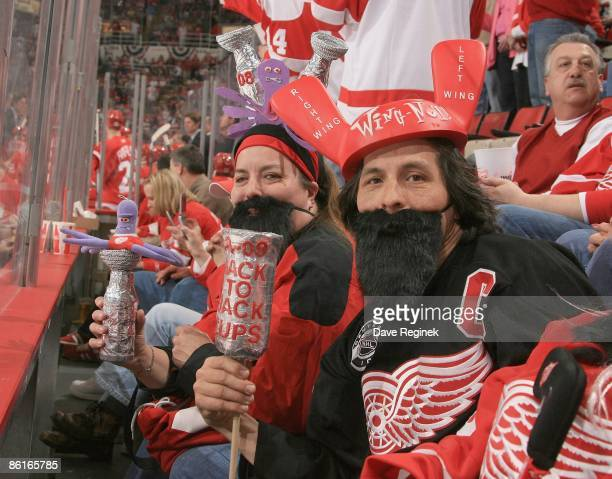 Rick and Kim Wu sport playoff beard theme and display home made stanley cups while posing for a photo during Game One of the Western Conference...