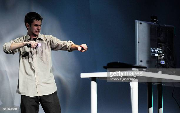 Rick Anton holds two playstation motion controlers during a demonstration at Sony's media breifing at the Electronics and Entertainment Expo on June...