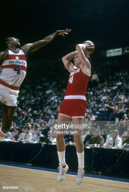 Rick Barry of the Houston Rockets looks to pass the ball over the out stretched arm of a Washington Bullets defender during a circa 1978 NBA...