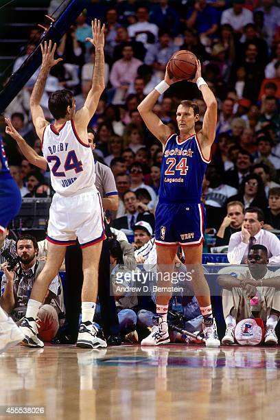 Rick Barry of the West Legends team inbounds the ball against Bobby Jones of the East Legends team during the Schick Legends Classic at AllStar...