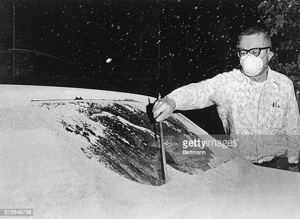 Rick Cole, director of emergency services for Yakima, wears a mask as he uses a snow brush to brush volcanic ash off of his auto's windshield. The...
