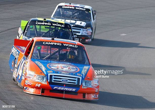 Rick Crawford driver of the Circle Bar/International Truck Engine Ford Ford leads a group of trucks intot turn one during the NASCAR Camping World...