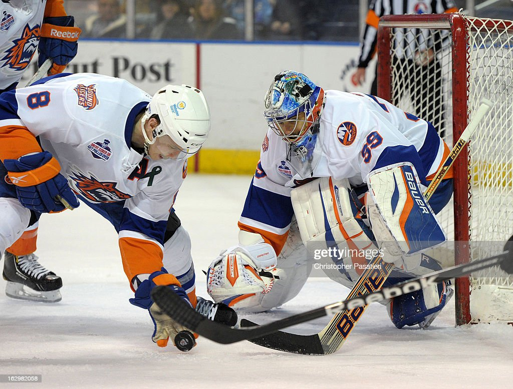 Rick DiPietro #39 of the Bridgeport Sound Tigers watches as Nathan McIver #8 clears the puck from the front of the net during an American Hockey League game against the Adirondack Phantoms on March 2, 2013 at the Webster Bank Arena at Harbor Yard in Bridgeport, Connecticut.