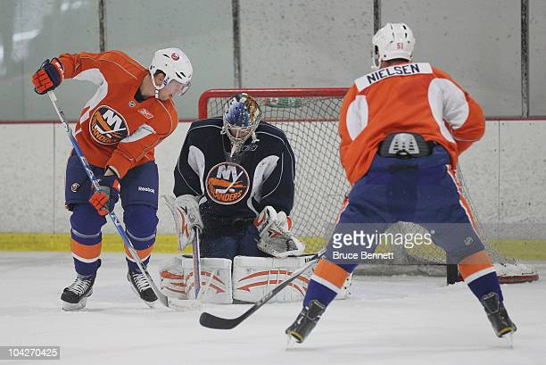 Rick DiPietro of the New York Islanders makes the save against Josh Bailey and Frans Nielsen during a training camp session at Iceworks on September...