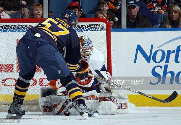 Rick DiPietro of the New York Islanders stops Tyler Myers of the Buffalo Sabres at the Nassau Coliseum on January 23 2011 in Uniondale New York