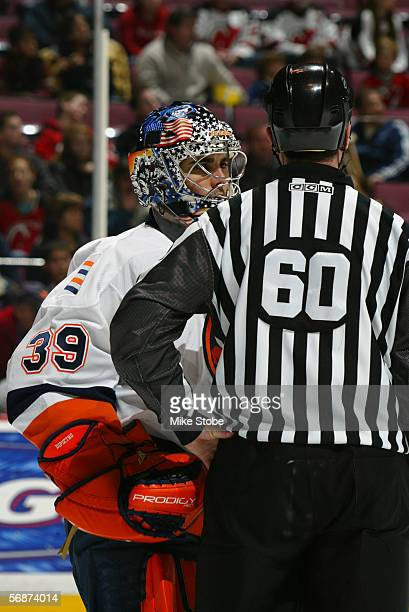 Rick DiPietro of the New York Islanders talks to lineman Pat Dapuzzo during the game against the New Jersey Devils at the Continental Airlines Arena...