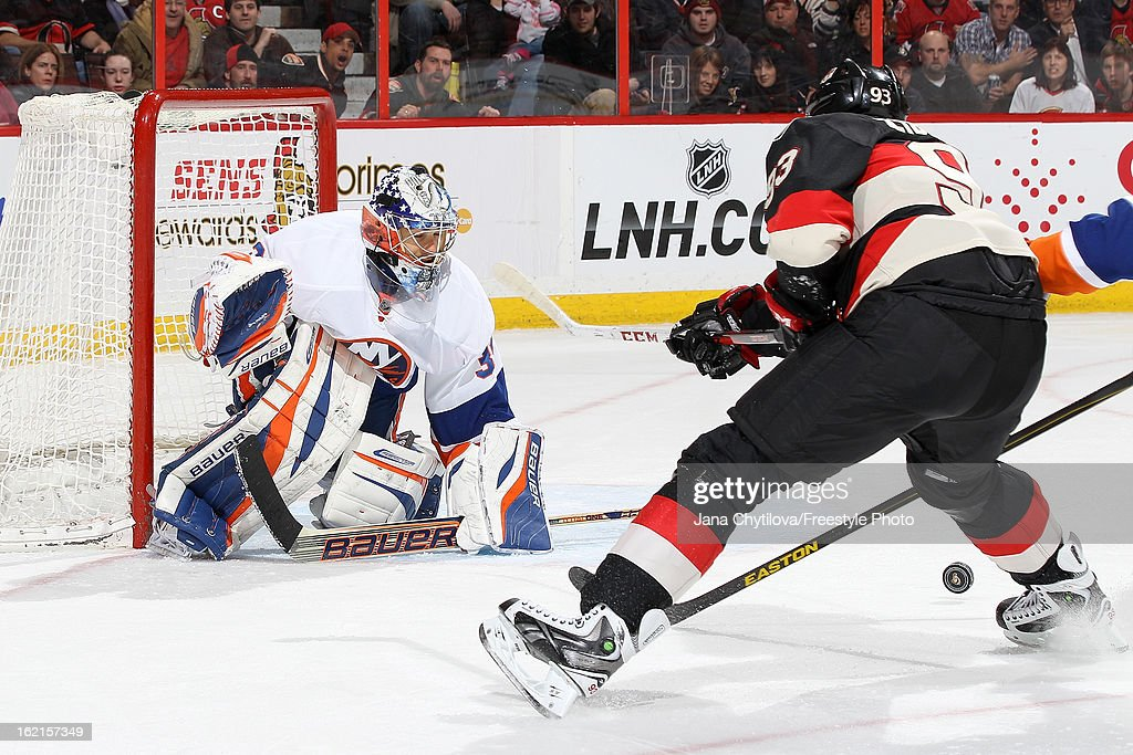 Rick DiPietro #39 of the New York Islanders watches the puck as Mika Zibanejad #93 of the Ottawa Senators fans on the shot, during an NHL game at Scotiabank Place on February 19, 2013 in Ottawa, Ontario, Canada.