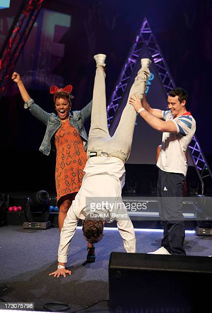 Rick Edwards does a handstand held up by Gemma Cairney and olympian Kristian Thomas on stage at vInspired Live a youth social change event at The...