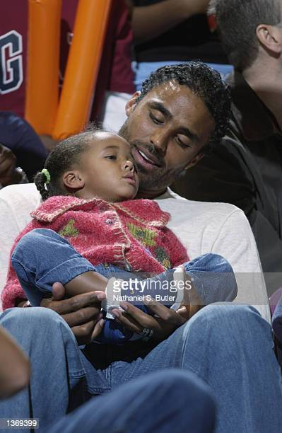 Rick Fox of the Los Angeles Lakers and his daughter watch Game one of the 2002 WNBA Finals between the Los Angeles Sparks and the New York Liberty on...
