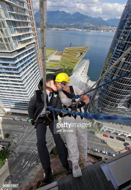 Rick Harker and Marlene Hoar kiss as they repel down the side of a skyscraper as part of their wedding ceremony September 15 2009 in Vancouver...
