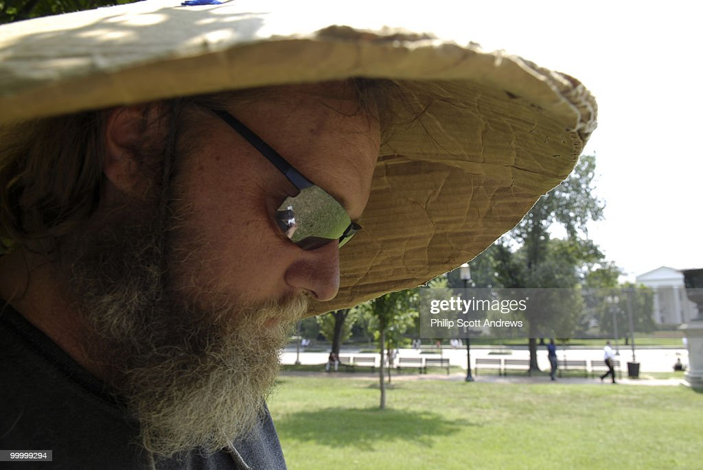 Rick (Richard Allen) Hohensee finds shade under a cardboard hat as he stands outside the White-house to protest both the war in Iraq and the recent dispute between Israel and Lebanon. Temperatures in Washington D.C. are expected to climb to around 100 degrees this week.