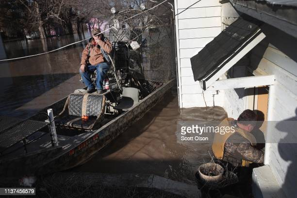 Rick Johnson helps Larry Whetsel recovers possessions from his flooded home on March 21 2019 in Craig Missouri The town of Craig is completely...