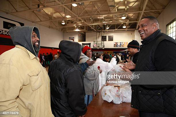 Rick Mahorn and a fan attend the 2013 AllStar Giveback Thanksgiving Edition at Don Bosco Hall on November 26 2013 in Detroit Michigan
