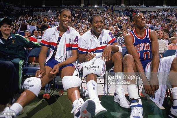Rick Mahorn, Mark Aguirre, and Dennis Rodman of the Detroit Pistons watch the game as they rest on the bench during a game against the Milwaukee...