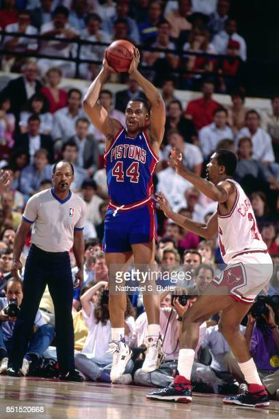 Rick Mahorn of the Detroit Pistons passes the ball against Bill Cartwright of the Chicago Bulls circa 1989 at Chicago Stadium in Chicago, Illinois....