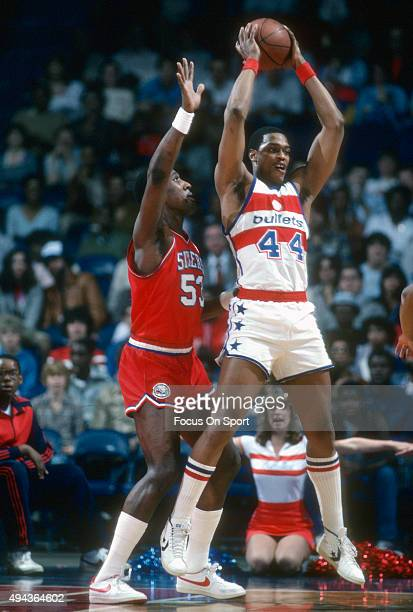 Rick Mahorn of the Washington Bullets looks to pass the ball while guarded by Darryl Dawkins of the Philadelphia 76ers during an NBA basketball game...