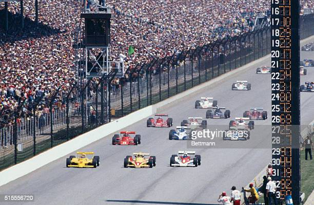 Rick Mears , who won the pole position, leads field at the start of the Indianapolis 500, which he won. Front row cars are Unser , Sneva , Mears .