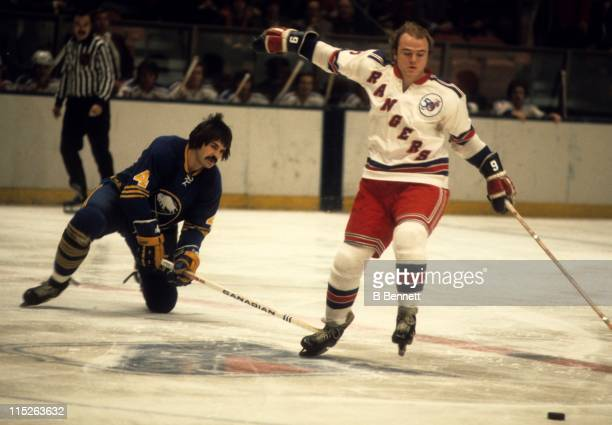 Rick Middleton of the New York Rangers goes for the puck while Jerry Korab of the Buffalo Sabres slashes him during their game on January 28 1976 at...