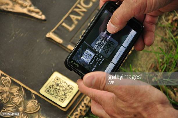 Rick Miller cofounder of Digital Legacys reads a QR code attached to a memorial plaque at Sunset Memorial Park in Philadelphia Pennsylvania June 16...