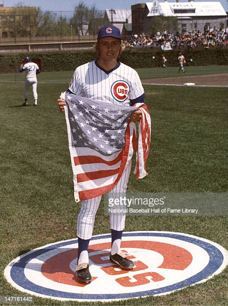 Rick Monday of the Chicago Cubs holding an American flag before a National League game during the 1976 season at Wrigley Field in Chicago Illinois