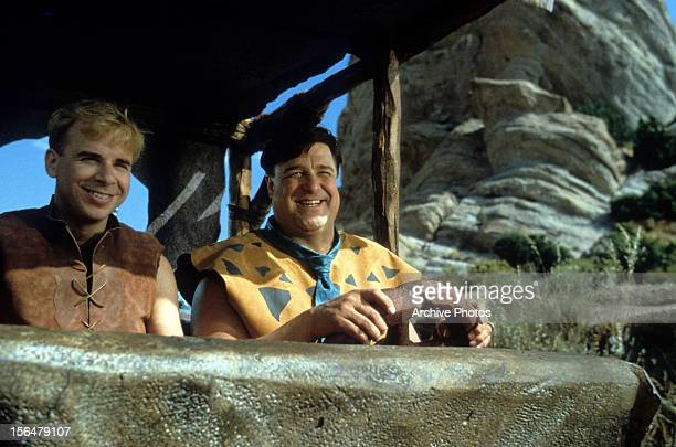 Rick Moranis and John Goodman riding together in a scene from the film 'The Flintstones' 1994